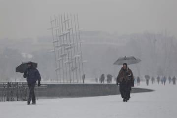 ギリシャ北部テッサロニキで、雪が降る中、遊歩道を行き交う人々=9日(ロイター=共同)