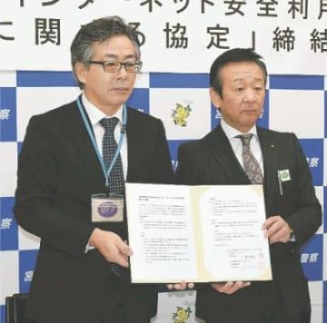 協定書を掲げる一條支店長(左)と遠藤部長