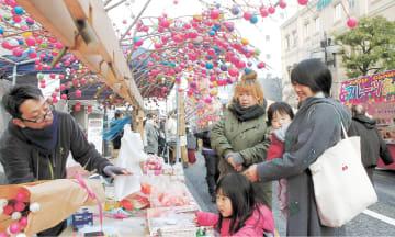 初市で色鮮やかな団子木を買い求める買い物客ら=山形市七日町