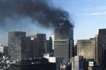 火災で黒煙を上げる建設中の高層ビル=11日午後2時12分、東京・新橋