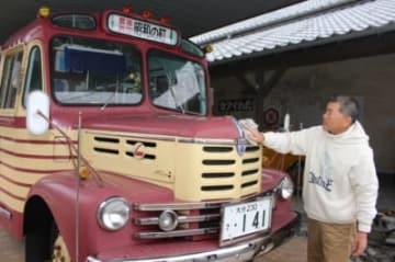 昭和ロマン号を磨く運転手の清原一義さん=豊後高田市新町