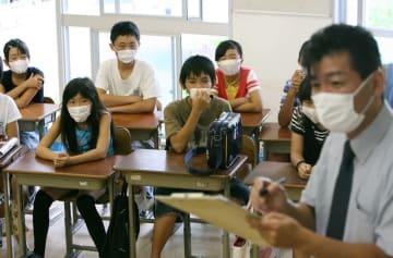 新型インフルエンザの感染予防のためマスクを着け、担任教諭に体調を報告する児童=長崎市立橘小