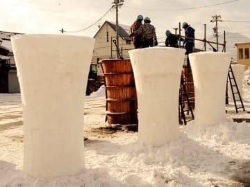 作業現場に次々と並ぶ高さ2メートルの雪像ろうそく=飛騨市古川町若宮、市営駐車場