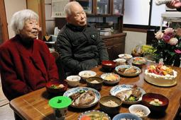 恵子さんの誕生日を祝う有本明弘さん(右)と嘉代子さん=12日午後、神戸市長田区
