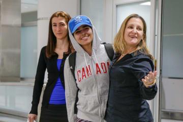 カナダ・トロントの空港に到着したラハフ・ムハンマド・クヌンさん(中央)とカナダのフリーランド外相(右)=12日(ロイター=共同)