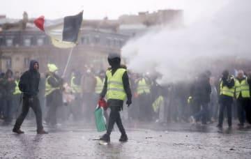 パリの凱旋門近くで、警官隊が放水する中、デモを行う黄色いベスト運動の参加者ら=12日(ロイター=共同)