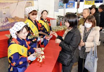水仙娘から水仙を受け取る来場者=1月12日、福井県南越前町の河野シーサイドパーク