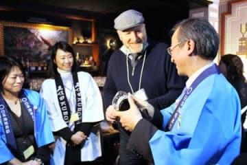 来場したNYのバイヤーに日本酒などを勧める花角英世知事(右)=11日、NYマンハッタン