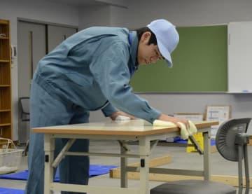 清掃サービス部門の検定でテーブルを丁寧に拭き上げる生徒=12日午前、松山市西垣生町