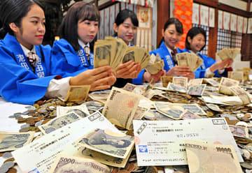 拝殿でさい銭の一部を勘定する行員ら=12日、大阪市浪速区の今宮戎神社