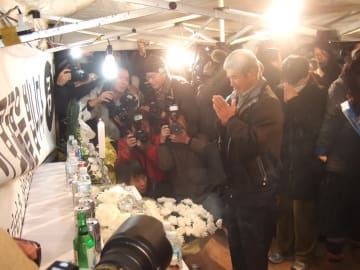 火災現場の献花台に花を手向け、手を合わせる被害者の家族=釜山市