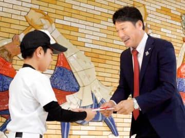 代表児童に野球道具の目録を手渡す中根代表(右)