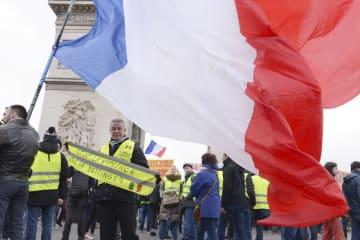 12日、パリの凱旋門前で黄色いベスト運動のデモに参加する男性ら(共同)