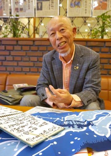 机の上に「根多帖」や落語家の手ぬぐいを広げ、「今年も楽しみたい」と話す前田さん=長崎新聞社