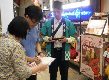 地元消費者に味や価格などの聞き取りを行う千葉県立農業大学校の学生。試食後、サイズ違いで複数購入する買い物客の姿も見られた。=12日、クアラルンプール(NNA撮影)
