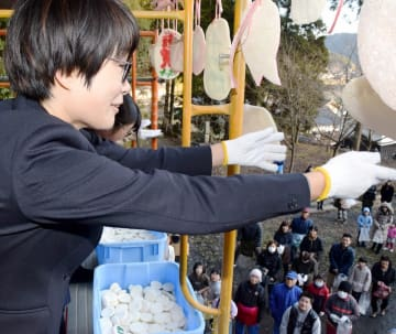 おこないで餅をまく女性=1月13日、福井県鯖江市磯部町の石部神社