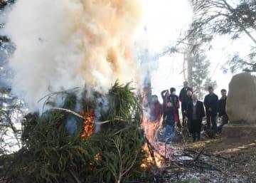勢いよく上がる煙の方向を見守る住民