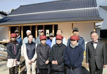 3月のオープンに向けて工事が進む寛政蔵と、山下泰雄社長(右端)ら通潤酒造の従業員=山都町