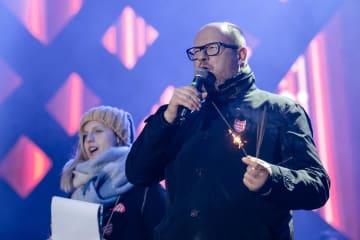 13日、ポーランド北部グダニスクで開かれたチャリティーイベントで発言するアダモウィチ市長(右)(ロイター=共同)