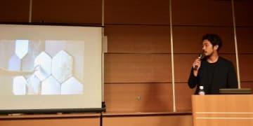 「世界学生環境サミット」で、パナソニックとのコラボ事例(西陣織に触れるだけで操作できるスピーカー「織ノ響 ori-no-hibiki」)を紹介する細尾真孝氏