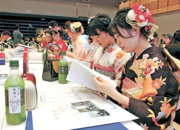 津波対策の活動などをまとめた「女川いのちの教科書」を手にする新成人