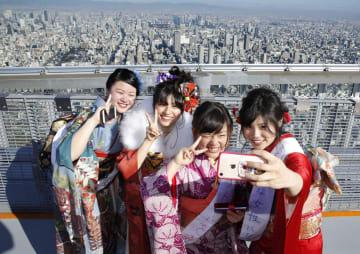 「あべのハルカス」展望台までの階段を上りきり、記念撮影する振り袖姿の新成人たち=14日、大阪市