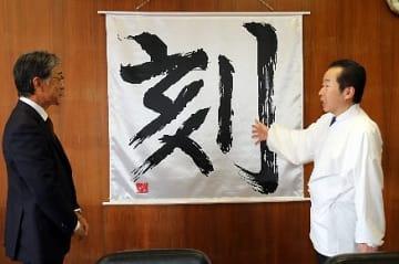 【真砂充敏市長(左)に「刻」の一文字に込めた思いを語る九鬼家隆宮司=和歌山県田辺市役所で】