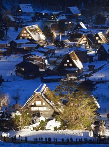 ライトアップが始まり、幻想的に浮かび上がった白川郷の合掌造り集落=14日夕、岐阜県白川村