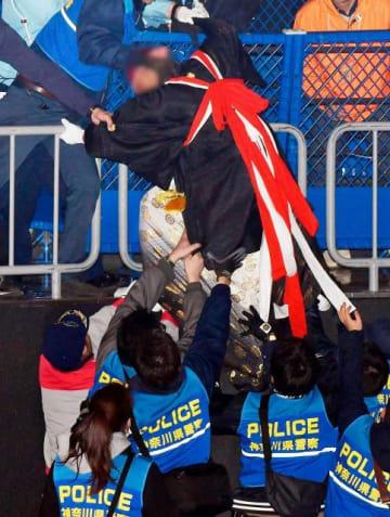 ステージに上がろうとし、警備員らに制止される新成人。約10分間式典が中止された=14日、横浜市港北区の横浜アリーナ