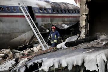 貨物機が着陸に失敗し大破した現場で活動する救助関係者=14日、イラン・アルボルズ州の空港(AP=共同)