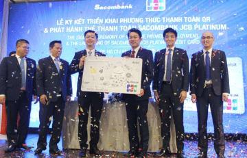 JCBがベトナムで初めてQRコード決済を導入した。調印式を行ったJCBIベトナムの山口代表(写真中央・右)とサコムバンクのグエン・ミン・タム副頭取(同・左)ら関係者=14日、ホーチミン市