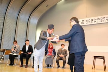 【岩崎学長(右)から賞状を受け取るクンワルさん=四日市市萱生町の四日市大学で】