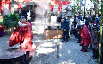 【熱湯に浸したクマザサを勢いよく振り、参列者に湯玉を浴びせる金子宮司(左)=伊勢市二見町江の栄野神社で】