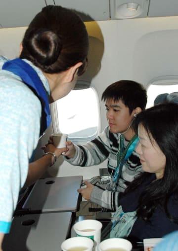 ANA2019便の機内で客室乗務員からドリンクサービスを受ける参加者
