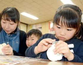 紙やすりでおもちゃの表面を滑らかにする参加者