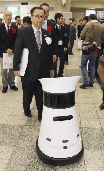 岐阜県大垣市役所で自律走行型ロボットから誘導を受ける小川敏市長(手前)=15日午前