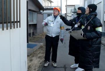 空き家とみられる建物の外観を調べる山田賢二選手(右)と穂積選手(中央)