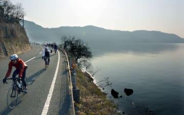 自転車でビワイチ(琵琶湖一周)を楽しむ愛好者でにぎわう湖岸沿いの道路(滋賀県長浜市)