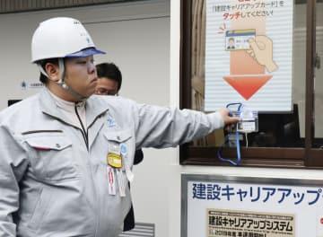 試験運用が始まった建設キャリアアップシステムのカードをかざす建設作業員=15日午後、東京都千代田区