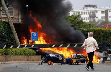 15日、爆発と銃撃音があったケニア・ナイロビの高級ホテルの敷地内で炎上する車(ロイター=共同)