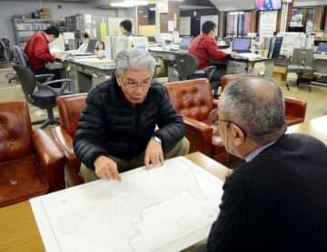 作木支所で打ち合わせをする田村さん(手前左)。広い庁舎内で職員はまばらだ