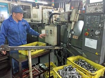 部品加工機械の動作を確認する高崎冶金工業の干川さん