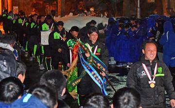 メダルを胸に掲げ、拍手で迎えられる青森山田の選手ら=15日午後5時半ごろ、青森市の青森山田高校