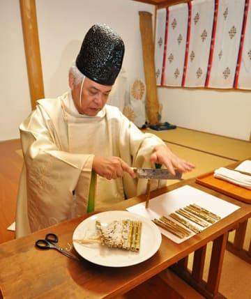 米の入ったササダケを割る牛丸大吾宮司=高山市一之宮町、飛騨一宮水無神社