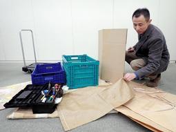 段ボール、大型の紙袋、がら袋…。生前整理で便利な道具を広げる宇仁菅真志さん=加古川市加古川町北在家