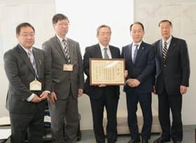 賞状を手に記念写真に収まる岩倉社長(中央)