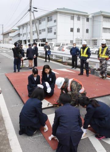 「ハンプ」と呼ばれる段差の設置作業。三日月小(奥)の児童たちが作業を手伝った=小城市三日月町