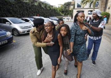 15日、ナイロビで襲撃されたホテルから避難する市民ら(AP=共同)
