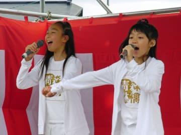 初めてのステージで手をつないで歌う、10歳のころの王林さん(右)とときさん。規律第一に、10年以上のキャリアを積んでいまがある=2008年8月(提供・リンゴミュージック)