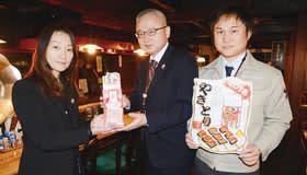 寄付金を手渡す石塚代表取締役(左)